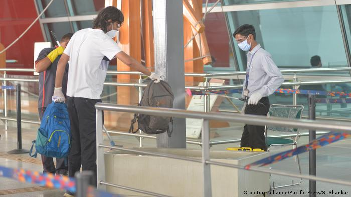 Airport official sprays disinfectant on the baggage of a passenger before he enters for check-in at Indira Gandhi International Airport in New Delhi.
