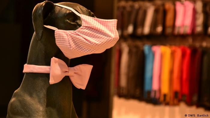 A dog mannequin wearing a pink checkered bow tie and facemask