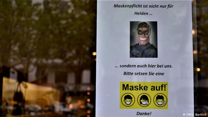 A sign asking customers to wear a mask with a picture of a super-hero