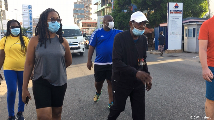 Joseph Hammond walks with supporters through the streets of Accra