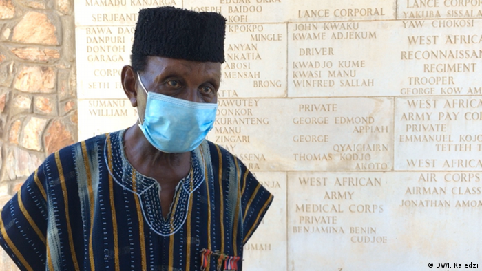 Joseph Hammond, wearing a mask, stands in front of a war memorial in Accra