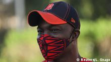 A man looks on as he wears a protective face mask with colors matching his clothes, amid the coronavirus disease (COVID-19) outbreak, in Angre area of Abidjan, Ivory Coast May 13, 2020. Picture taken May 13, 2020. REUTERS/Luc Gnago