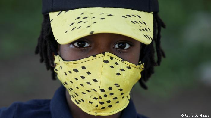 Um menino usa um chapéu e uma máscara criados pelo estilista marfinense Arthur Bella N'guessan