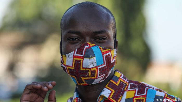 Ivorian designer Arthur Bella N'guessan wears a face mask with color matching his clothes