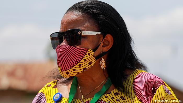 A woman wears a mask made from the same fabric as her dress