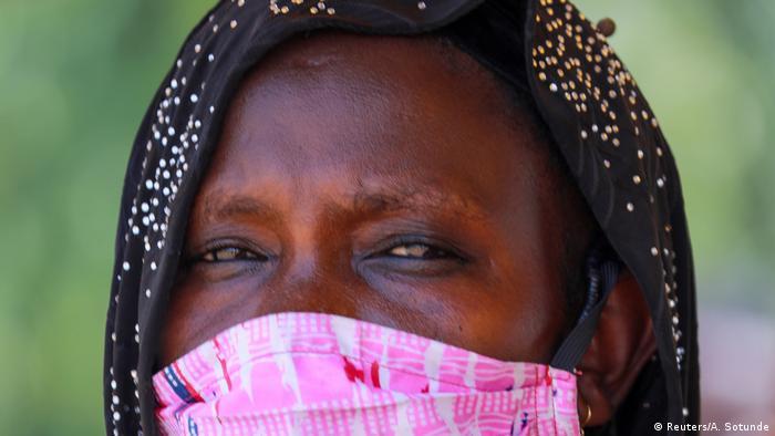 Em Abuja, uma mulher usa uma máscara rosa com seu hijab