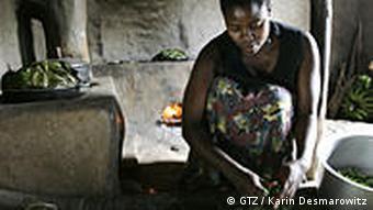 Ugandische Frau mit Rocket Stove-Ofen