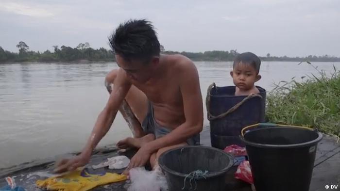 Ein Kleinkind sitzt in einem Wassereimer am Flussufer in Rukam in Indonesien. Ein Mann wäscht seine Wäsche.