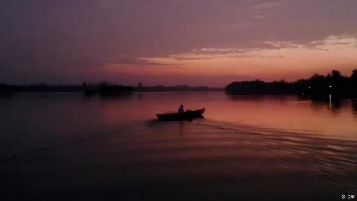 Ein Boot fährt im Sonnenuntergang auf dem Fluss bei Rukam in Indonesien