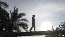 Rukam resident walks among palm oil plantation in Indonesia