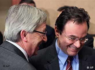 Greek Finance Minister Giorgos Papakonstantinou, right, talks with Luxembourg's Prime Minister and Chairman of the Eurogroup Jean Claude Juncker at the start of a Eurogroup meeting in Brussels, Monday, March 15, 2010. Eurozone finance ministers meet to check whether Greece's austerity program goes far enough to reduce its massive deficit, amid talk that they are preparing a rescue package for the country if it can't borrow from wary bond markets. (AP Photo/Geert Vanden Wijngaert)