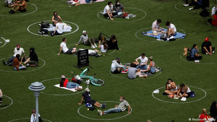 Pessoas sentadas em grupos em círculos desenhados em gramado