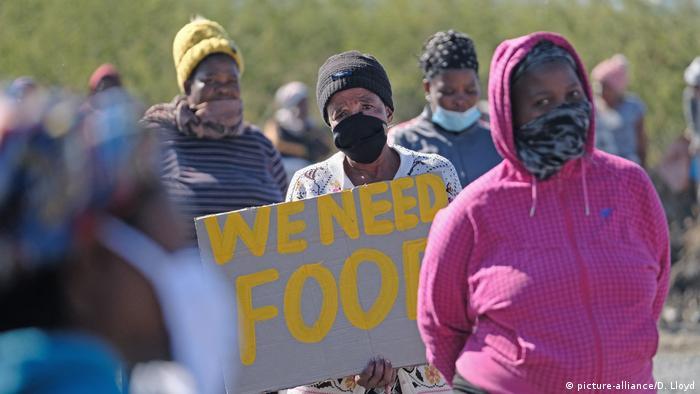 Pobladores de Rustenburg, en África del Sur, piden alimentos durante la cuarentena.