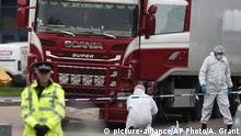 Forensic police officers attend the scene after a truck was found to contain a large number of dead bodies, in Grays, South England