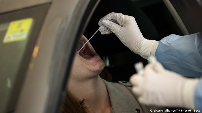 A person being tested - by another human being - at a drive-through coronavirus testing station