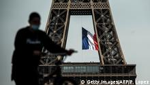 A man wearing a face mask pushes his bicycle on Trocadero Plaza as a French national flag flies on the Eiffel Tower in background in Paris on May 11, 2020 on the first day of France's easing of lockdown measures in place for 55 days to curb the spread of the COVID-19 pandemic, caused by the novel coronavirus. (Photo by PHILIPPE LOPEZ / AFP) (Photo by PHILIPPE LOPEZ/AFP via Getty Images)