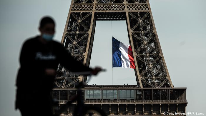 Man pushes bicycle next to Eiffel tower