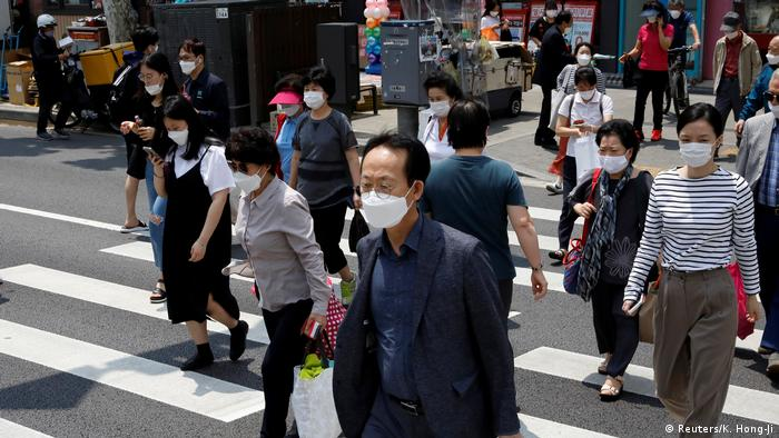 Pedestrians with facemasks crossing a street in Seoul