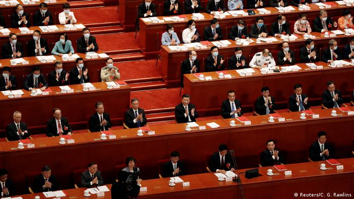 Chinese President Xi Jinping and other officials applaud after the vote on the national security legislation for Hong Kong Special Administrative Region at the closing session of the National People's Congress (NPC) at the Great Hall of the People in Beijing