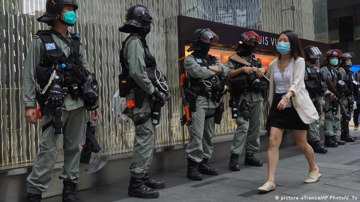 A woman walking past a row of police in riot gear (picture-alliance/AP Photo/V. Yu)