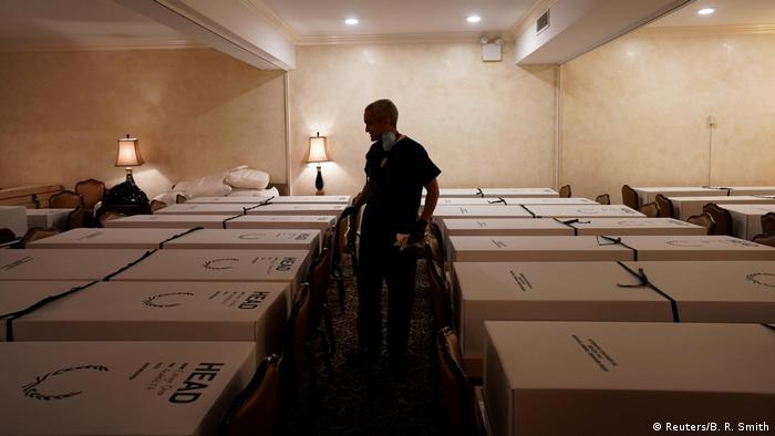 A funeral director with a mask looks over caskets of COVID-19 victims (Reuters/B. R. Smith)