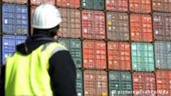A dock worker and a stack of containers