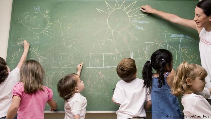 Crianças e professora diante de lousa