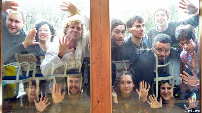 Ungefähr 12 Menschen schauen dem Photographen lächelnd durch eine Glasscheibe zu