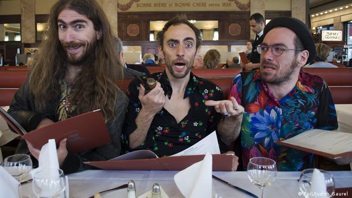 Drei flippig aussehende Musiker sitzen am Restauranttisch