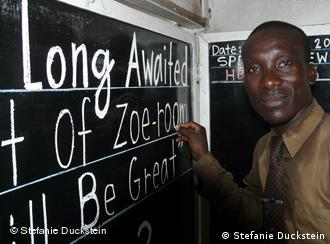 Alfred Sirleaf in front of his blackboard