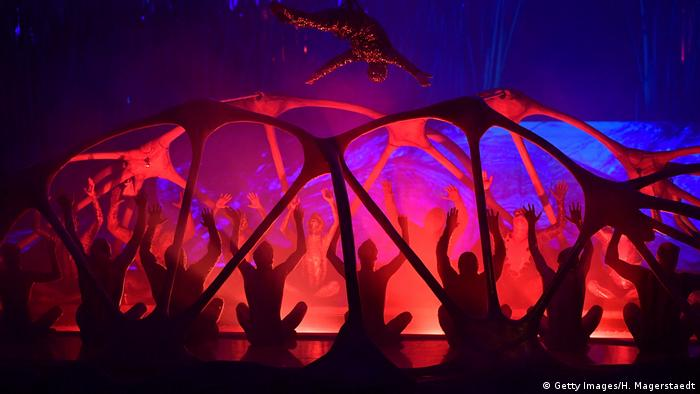 performers hold up their hands in a circus tent
