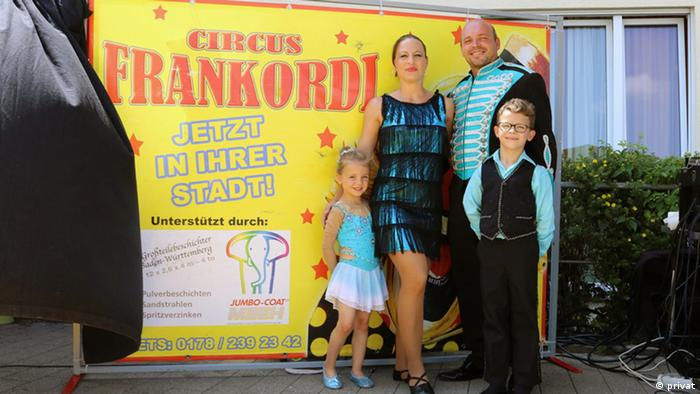 4 member circus family stand in front of a flyer
