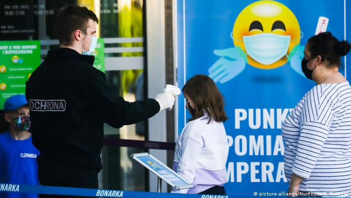 A guard measures the body temperature of customers entering a shopping mall in Krakow