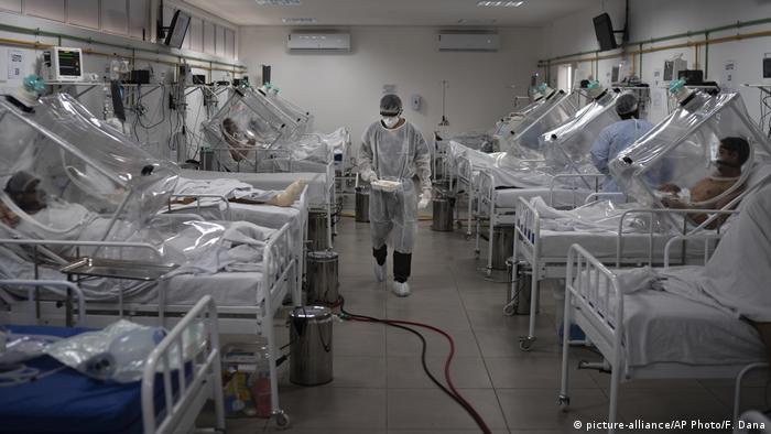Enfermeiro entre leitos com pacientes de covid-19