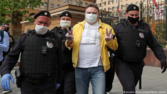 Police hold Plushchev by both arms