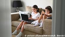 Schwester Mädchen, die mobile Geräte während der Selbstisolierung zu Hause verwenden