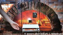 19.05.2020, Bayern, Augsburg: Ein Kunde greift nach einer Pizza Salami die nach etwa drei Minuten Backzeit aus einem Automaten ausgeworfen wird. In dem kleiderschrankgroßen Kasten mit Backofen lagern etwa 80 Pizzen in zwei Sorten (zu dpa: Große Nachfrage nach Pizza aus dem Automaten vom 29.05.2020). Foto: Karl-Josef Hildenbrand/dpa +++ dpa-Bildfunk +++ | Verwendung weltweit