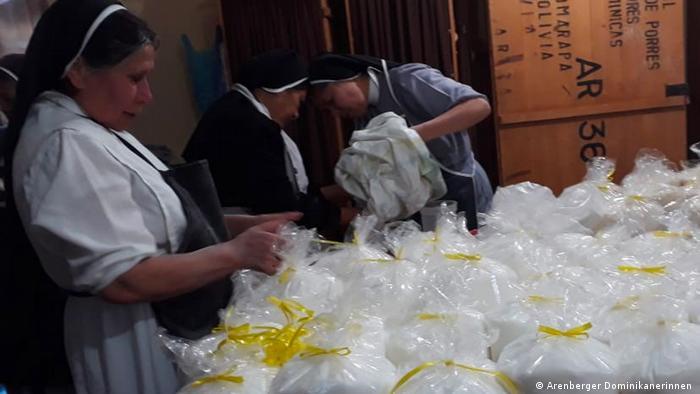 Varias hermanas preparan bolsas con alimentos para repartirlas entre familias que pasan hambre.