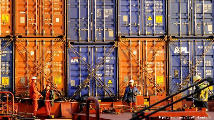 Im Hafen Hamburg machen Mitarbeiter Pause vor gestapelten Containern