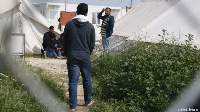 Multiple people stand amidst tents at the Pournara refugee camp in Cyprus