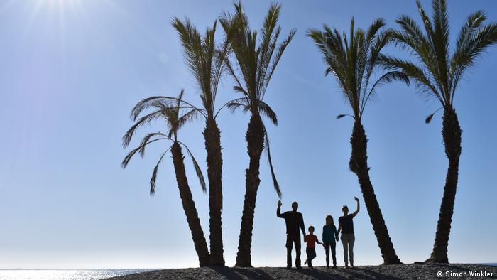 A family under palm trees waving at the camera