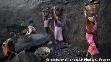 FILE - In this Jan. 7, 2011 file photo, people carry baskets of coal scavenged illegally at an open-cast mine in the village of Bokapahari in the eastern Indian state of Jharkhand. The global fleet of coal-fired power plants is projected to begin shrinking by 2022 as plant retirements outpace new construction, according to a new report that warns the heavily-polluting fuel's decline may not come quickly enough to meet international emission reduction goals. (AP Photo/Kevin Frayer, File)  