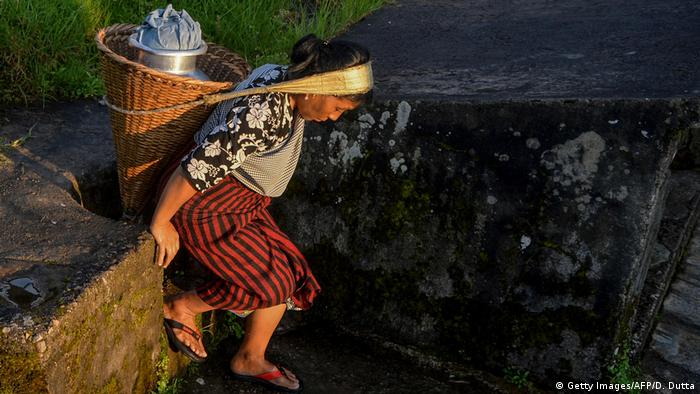 A woman carries a churn of water in a basket on her head