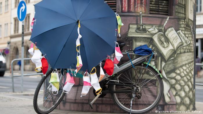 Ein Fahrrad, an dem Mundschutze hängen (picture-alliance/dpa/S. Kahnet)