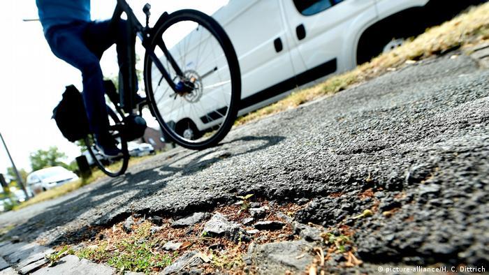 Ein Mann fährt mit Fahrrad auf einem asphaltierten Weg.
