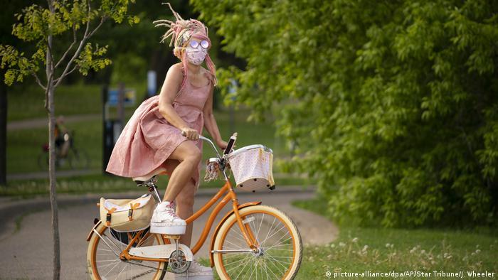 Eine Frau mit Mundschutz fährt mit einem Fahrrad (picture-alliance/dpa/AP/Star Tribune/J. Wheeler)
