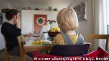Woman on the phone sits at a table with a young child