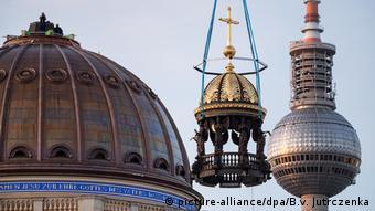 Ein Kran hebt ein Kreuz mit Engelsfiguren auf die kupferfarbene Kuppel des Humboldt-Forums (picture-alliance/dpa/B.v. Jutrczenka)