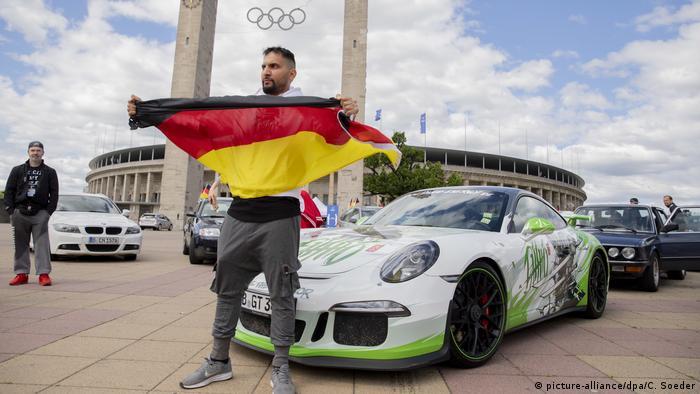 Attila Hildmann posiert mit Deutschlandf-Fahne und seinem Porsche vor dem Berliner Olympia-Stadion