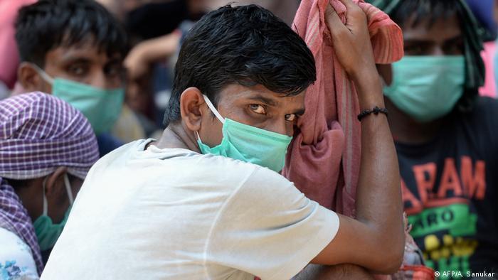 An Indian man wears a mask